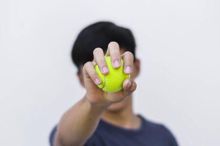男は、彼の顔にテニスボールを保持します。