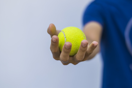 Man giving tennis ball in hand to you for play Stock Photo