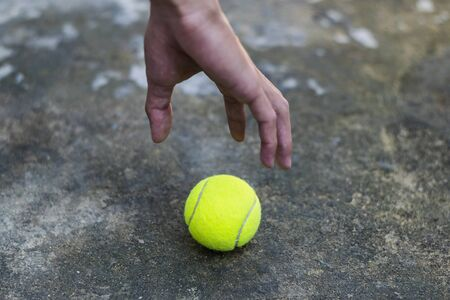 Hand picking tennis ball on the dirty ground