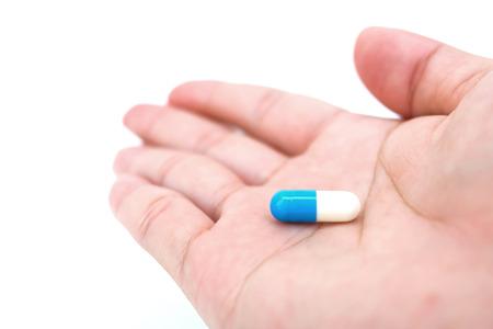 Blue white capsule of medicine on hand