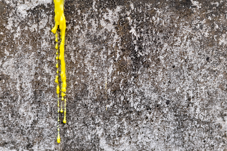 Yellow candle melt on the grunge concrete wall Stock Photo