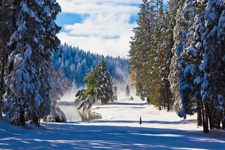 雪は山のゴルフコースのフェアウェイを覆われました。 写真素材
