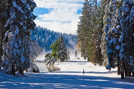 Snow covered fairway on a mountain golf course. Stock Photo