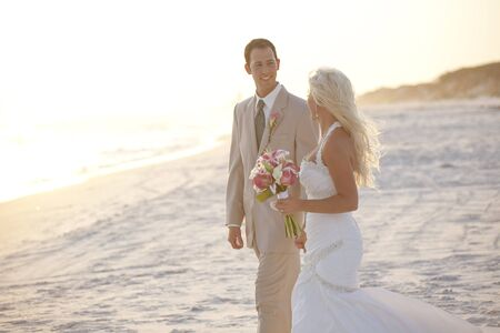 Bride and Groom Walking on the Beach photo