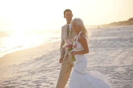 Bruid en Bruidegom Wandelen op het strand Stockfoto
