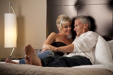 luxury bedroom: Man and Woman Relaxing in a Hotel Room Stock Photo