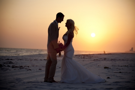 beach kiss: Bride and Groom at Sunset Stock Photo