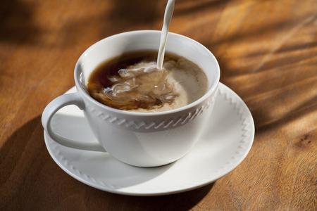Tasse Kaffee und Gießen Creamer Standard-Bild