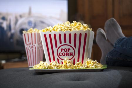 Recipiente grande de palomitas de maíz con los pies de la persona relajándose frente al televisor
