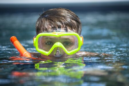 Young Boy with snorkel and diving mask in a swimming pool 스톡 콘텐츠