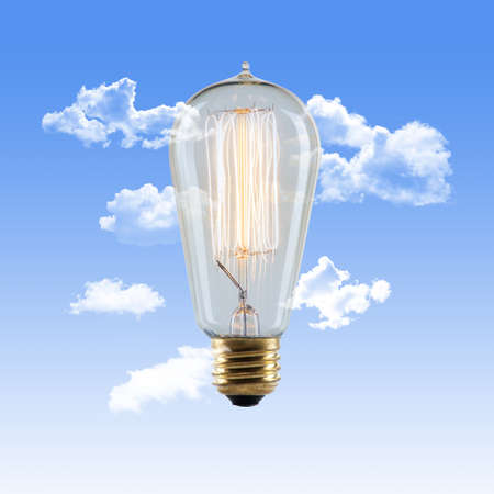 Vintage Edison Lightbulb with Glowing Filament on a Blue Sky Background with Clouds