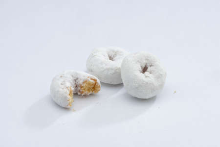 White Powdered Sugar Donuts on a White Background