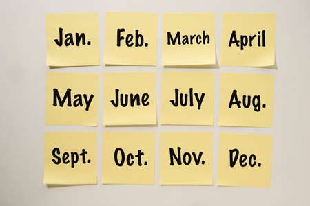 Yellow Sticky Notes Lined up on a White Background with the Months of the Year Written on them 免版税图像
