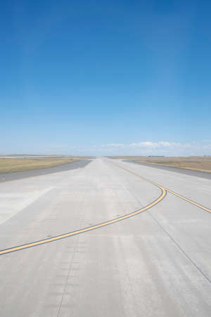 Empty Airport Runway on a Sunny Day with Vivid Blue Sky