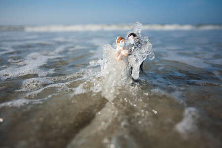 Bride and Groom Wedding Cake Topper with Surgical Masks Being Hit with a Wave in the Ocean Archivio Fotografico