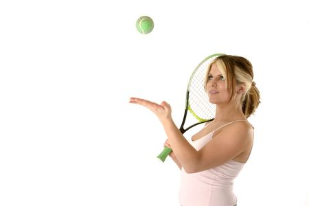 female tennis player tossing a ball in the air while holding her raquet Imagens