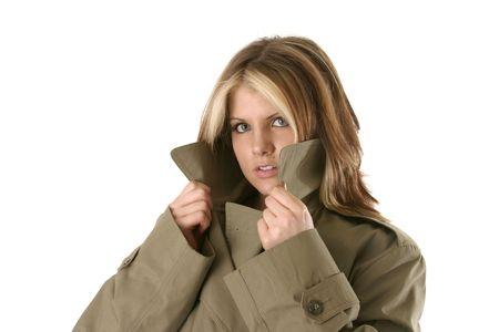 vrouwelijke prive-detective peering over haar trench coat Stockfoto