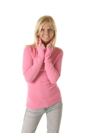 Pretty blonde woman smiling , while wearing a fuzzy pink sweater and pulling on the collar