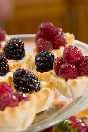 sweet dessert pastry cups filled with cream, blackberries and raspberries Banco de Imagens