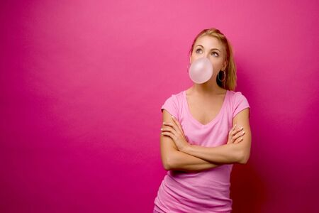 Girl in pink, blowing a big bubble against a pink background. Stock fotó
