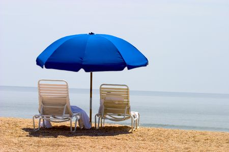 two empty beach chairs on the beach overlooking the ocean, with towels and a blue umbrella