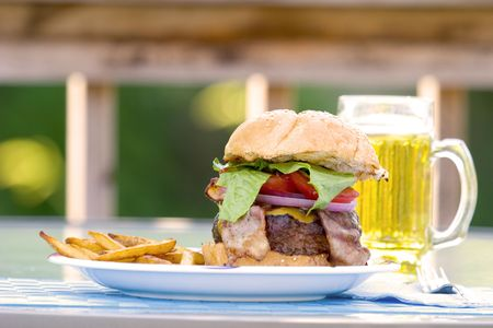 all american burger: Big Bacon Cheeseburger with lettuce, red onion and tomato on a sesame seed bun. Resting on a plate outdoors, with a beer. Stock Photo