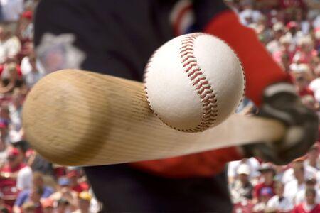 野球選手はバック グラウンドで群衆の中に彼のバットでボールを打つ