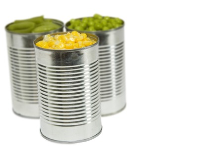 three cans of vegetables, corn, peas and green beans with blur separating back two cans