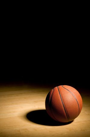 basketball resting on the hardwood floor in the spotlight with black copy space above