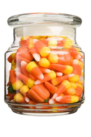 candy-corn and pumpkin filled glass jar Imagens