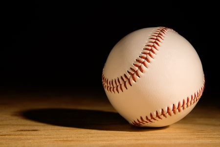 single baseball on wood plank coming out of the shadows photo