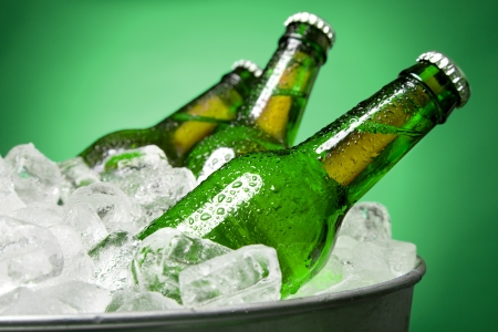 Three green bottles of beer chilling on ice in a tub against a green background