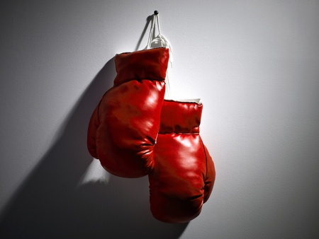 hand gloves: One pair of red boxing gloves hanging from the wall
