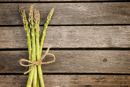 twine: Fresh asparagus on wood plankcs tied with twine