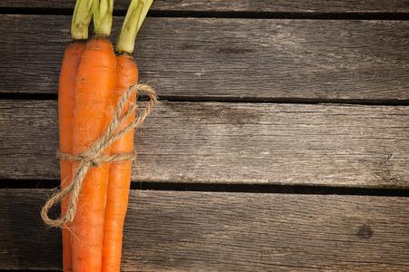 three farm fresh organic carrots tied with twine on wood planks