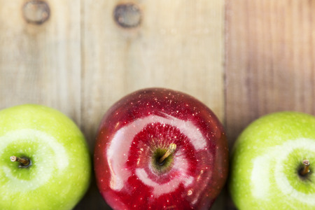 granny smith: over top view of three farm fresh organic  granny smith and red delicious apples from Michigan on wood planks Stock Photo