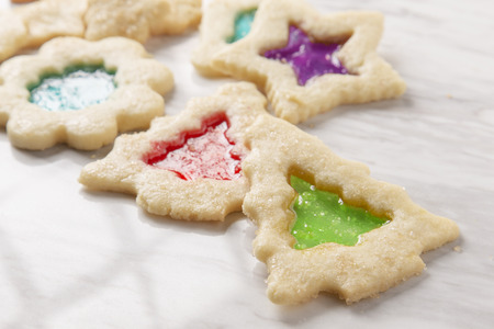 brightly colored stained glass christmas cookies on marble Stock Photo