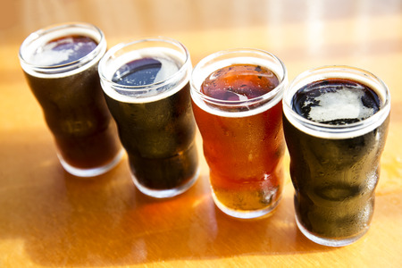 flight: four glasses of craft beer on wood table top