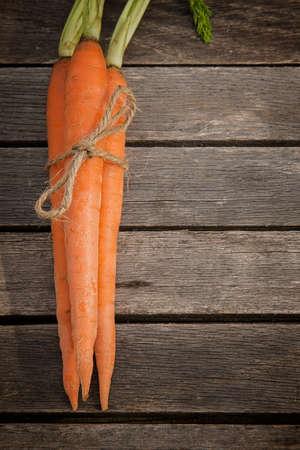 zanahoria: tres zanahorias orgánicos frescos de granja atados a la venta en los tablones de madera verticales edición