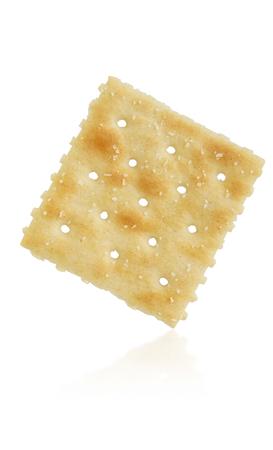 galletas: una sola galleta de soda en el fondo blanco con la reflexión Foto de archivo