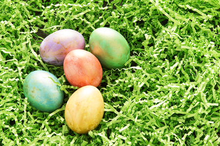 nestled: easter eggs with gold highlights nestled in green colored paper grass