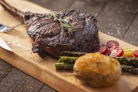 a bone-in tomahawk ribeye steak meal with twice baked potato, asparagus, tomatoes and sprig of rosemary on a wood plank over wooden background, angled view