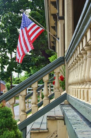 american flag flying from a front porch photo