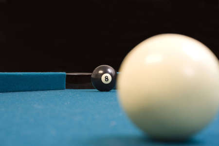 aiming for the 8 ball in the corner pocket to win photo