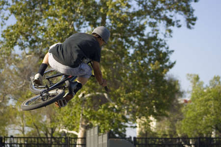 maneuver: teen performs a bicycle trick off a halfpipe