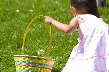 young girl reaches down for an easter egg while holding basket photo