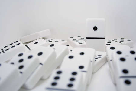 one domino still stands after others have fallen Stock Photo
