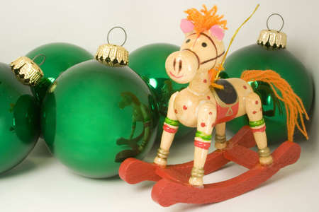 wooden rocking horse ornament and green baubles with brass loops