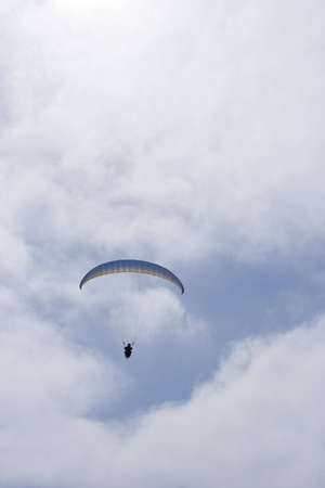 tandem paraglider soaring through the clouds