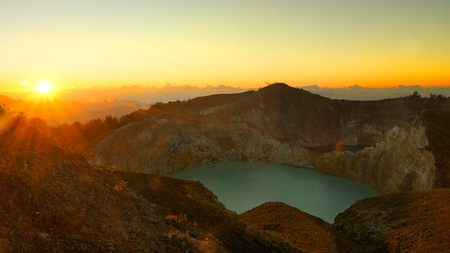 High panoramic view of the green turquoise colored lake in the volcano Kelimutu during the morning at sunrise with nobody around, Indonesia.